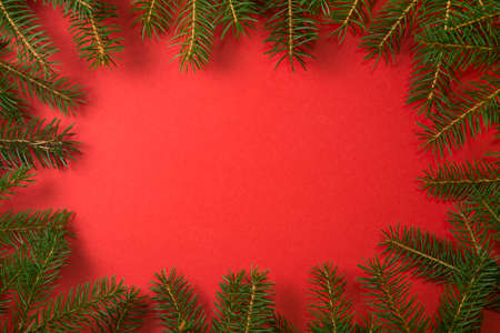 Christmas frame red background. Natural fir tree border with copy space for holiday design. Template for New year Imagens