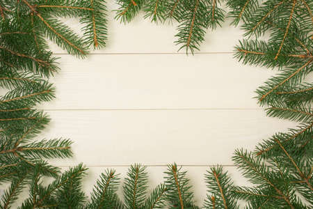Christmas tree frame branches on wooden background with copy space. Horizontal template top view for design