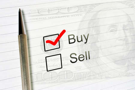 buy choice or sell, marked check box with a pen on lined paper dollar background closeup. Trade business resale concept