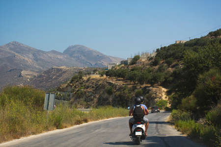Travelers couple on scooter riding a mountain road. Crete island, Greece. Romantic discovering the world Stock Photo