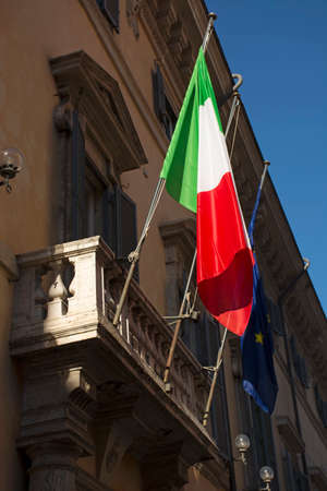 Flag of Italy and European Union on balcony of old building closeup at sunny day Stock Photo