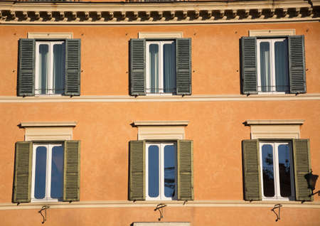 Windows and shutters of ancient Rome, old buildings facade brick color. Roman ancient architecture