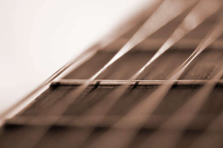 Guitar fretboard and strings blurred background closeup