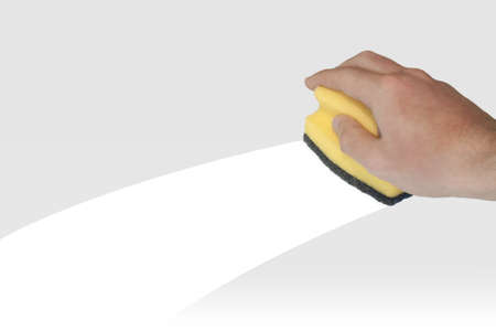 Hand with yellow sponge isolated on grey background and white clean track Stock Photo