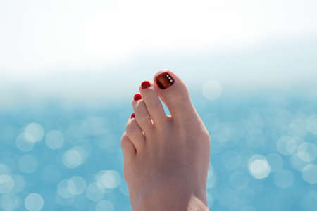 Female foot over blue ocean on sunny summer day Stock Photo