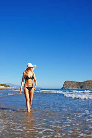 Young smiling blond caucasian white woman wearing black bikini, hat and sunglasses. Beach as background. 3/4 view. Model walking on a beach, looking aside to the sea. Copyspace. Stock Photo - 5319934