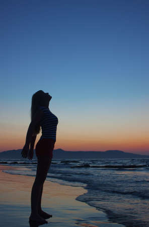 Silhouette of a young woman standing on a beach at sunset. Model looks up. Side view.