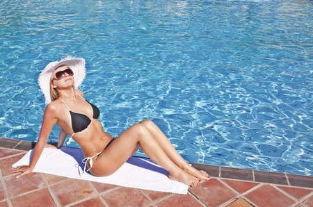 Young blond caucasian white woman wearing black bikini, hat and sunglasses. Model sitting at swimming pool. 34 view. photo