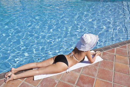 Young blond caucasian white woman wearing black bikini, hat and sunglasses. Model lying at swimming pool. 34 view.