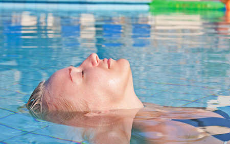 Young blond caucasian white woman floating in swimming pool. Side view. photo