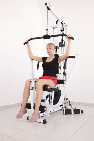 Young blond caucasian woman working out in gym. Pumping iron while sitting, lifting weight exercise. 34 view. Serious facial expression. Model looks aside. Stock Photo