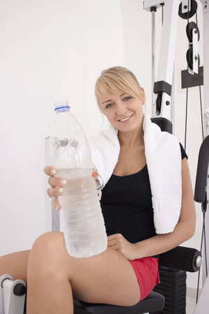 Young blond caucasian woman after workout in gym. Smiling model holds bottle with clear drinking water. Happy facial expression. Model looks at viewer. Bottle on foreground is out of focus. photo