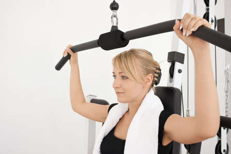 Young blond caucasian woman working out in gym. Pumping iron while sitting, lifting weight exercise. 34 view. Serious facial expression. Model looks aside. Closeup. Stock Photo