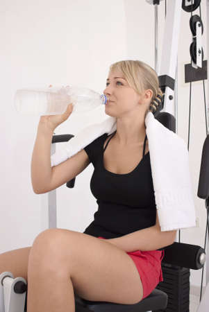 Young blond caucasian woman working out in gym. Smiling model holds bottle with clear drinking water. 34 view. Happy facial expression. Model looks aside. Stock Photo