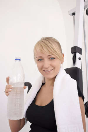 Young blond caucasian woman after workout in gym. Smiling model holds bottle with clear drinking water. Happy facial expression. Model looks at viewer. Bottle on foreground is out of focus. Portrait.