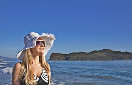 Young smiling blond caucasian white woman with hat and sunglasses. Clear blue sky, sea and island as background. 34 view. Model looks aside to the sun. Copyspace.