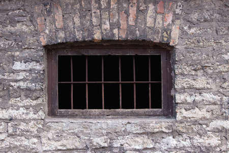 Old rusty prison window. Brick wall Stock Photo