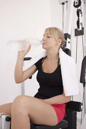 Young blond caucasian woman working out in gym. Model holds bottle with clear drinking water. 34 view. Serious facial expression. Model closed eyes.