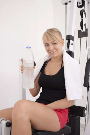Young blond caucasian woman working out in gym. Smiling model holds bottle with clear drinking water. 34 view. Happy facial expression. Model looks at viewer. photo