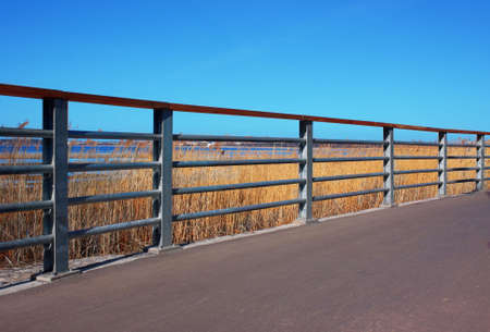 Perspective view of metal handrail, clear blue sky and walkway