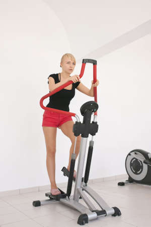 Young blond caucasian woman working out in gym. Stepping exercise. 34 view. Serious facial expression. Tired model looks aside. Stock Photo