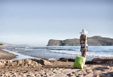 Young blond caucasian woman wearing white hat standing with green suitcase on a beach. Back view. Model looks at sea.