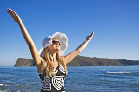 Young smiling blond caucasian white woman with hat and sunglasses holding spreading hands. Clear blue sky, sea and island as background. 34 view. Model looks aside to the sun. Copyspace.
