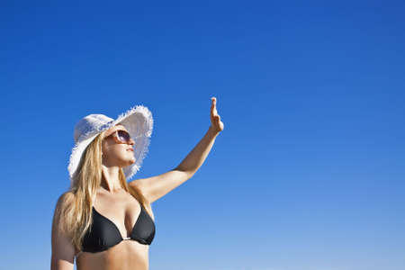 Young smiling blond caucasian white woman wearing black bikini, hat and sunglasses. Clear blue sky as background. Shot from below. Model streching hand, looking aside to the sun. Copyspace.