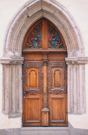 Old style brown wooden door with sculptures Stock Photo