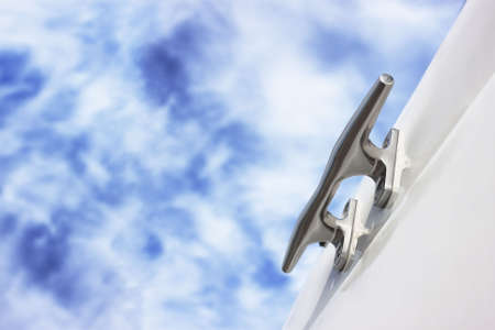 Shiny bitt on yacht board. Blue cloudy sky as background. No rope. Closeup. Stock Photo