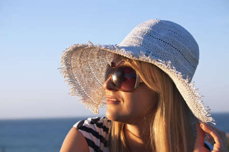 Young smiling blond caucasian white woman with hat and sunglasses looking at sunset. Clear blue sky and sea as background. Model looks aside. Profile portrait.