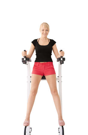 Young blond caucasian woman working out in gym isolate over white background. Abdominal prelum exercise. Happy facial expression. Smiling model looks at viewer.
