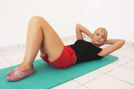 Young blond caucasian woman working out in gym. Abdominal prelum exercise. Happy facial expression. Smiling model looks at viewer.