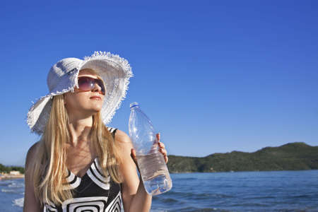 Young smiling blond caucasian white woman with hat and sunglasses holding bottle of water. Clear blue sky, sea and island as background. 34 view. Model looks aside to the sun. Copyspace. Stock Photo