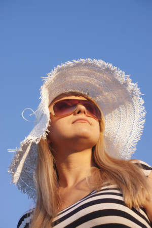 Young smiling blond caucasian white woman with hat and sunglasses. Wearing striped top. Clear blue sky as background. Shot from below. Model looks aside. Copyspace.