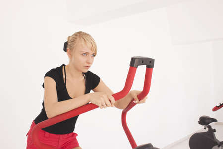 Young blond caucasian woman working out in gym. Stepping exercise. 34 view. Serious facial expression. Tired model looks straight.