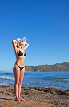 Young smiling blond caucasian white woman wearing black bikini, hat and sunglasses. Clear blue sky and sea as background. 34 view. Model standing, looking aside to the sun. Copyspace.