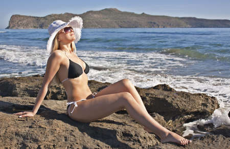 Young smiling blond caucasian white woman wearing black bikini, hat and sunglasses. Sea as background. 34 view. Model lying on a beach, looking aside to the sun. Stock Photo