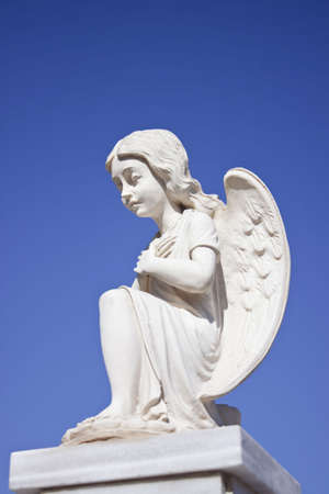 Statue of kneeled white angel crossing hands on chest. Clear blue sky as background. Shot from below. Copyspace.