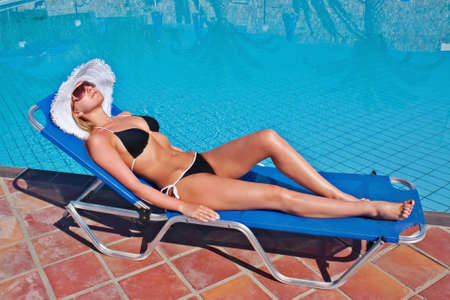 Young blond white woman lying on blue sunbed at swimming pool. Stock Photo