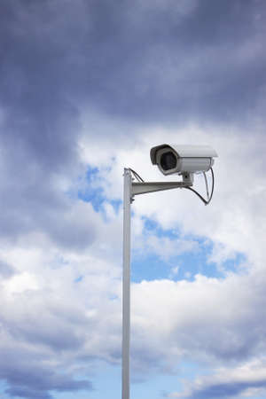 Surveillance security camera and cloudy sky as background photo