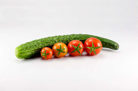 A cucumber and four tomatoes on the white background photo