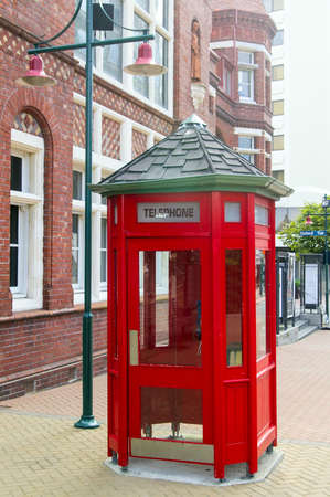 Red telephone booth at the street in Christchurch, New Zealand photo