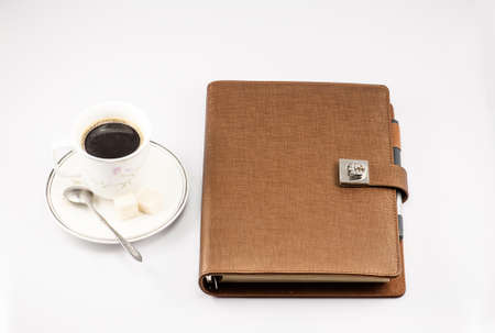 caffee: Notebook and a cup of coffee on the white background