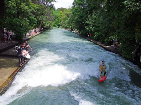 Munich, Germany - July 23, 2016 - Surfing at Eisbach, a small channel of the Isar River in Central Park