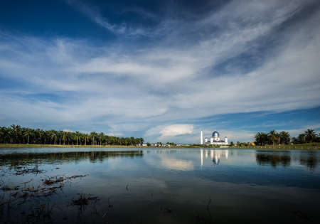 View of a lake with mosque in a distance Stock Photo