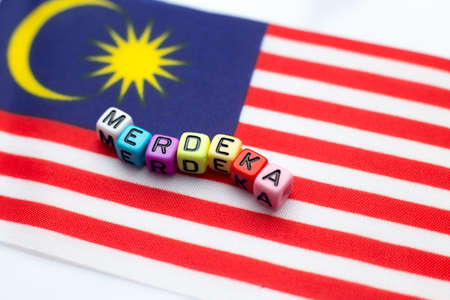 Malaysian flag with dice test wrote hari merdeka 版權商用圖片