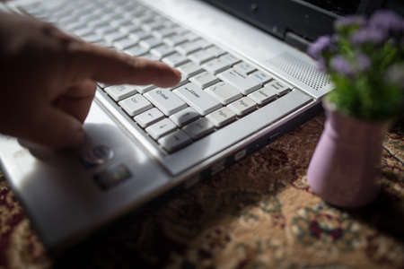 man finger about to press on enter key on laptop