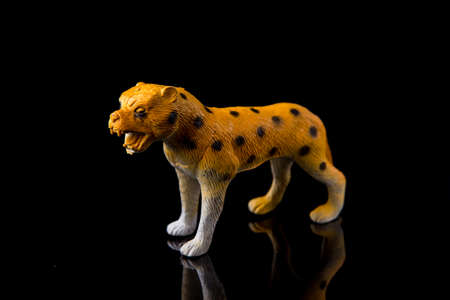 Cheetah toy figure on dark isolated background, selective focus, shallow depth