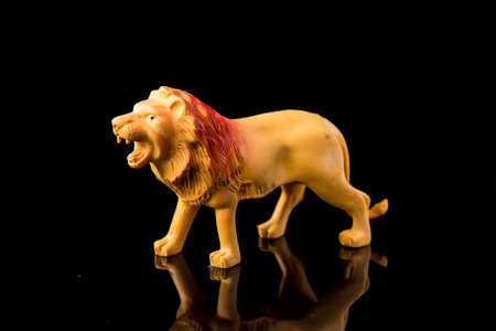 Lion toy figure on dark isolated background, selective focus, shallow depth